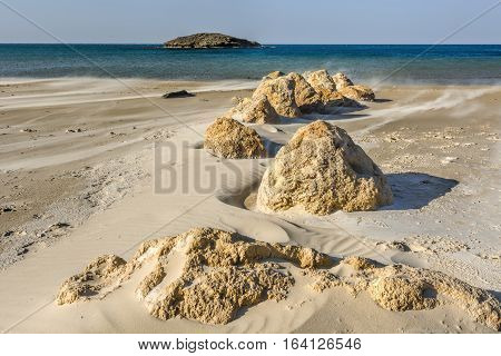 View of a small island from the Israeli shore of the Mediterranean Sea. Sand blowing over beach dune in wind in Israel