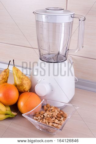 Blender With Fruits And Nuts On Kitchen Countertop