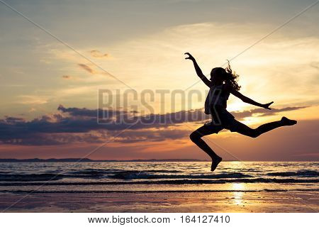 Happy girl jumping on the beach at the sunset time. Teenager having fun outdoors. Concept of life.