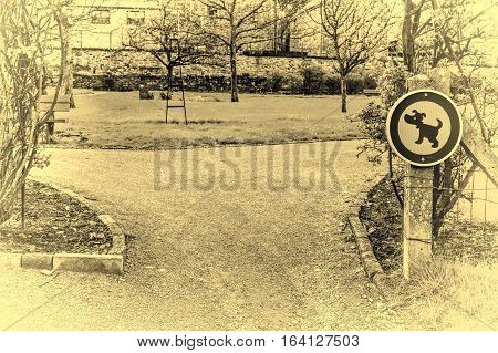 The sign prohibiting walking dogs in a park in Belgium. A sign telling you that this is not a dog toilet area. Vintage Style Toned Picture