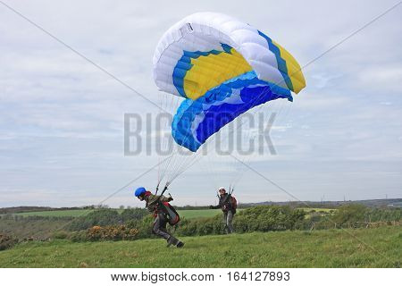 Paragliders ground handling their wings in a field
