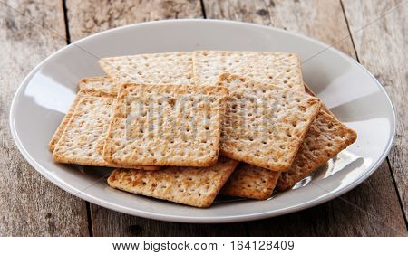 Cracker close up on white plate on wooden background