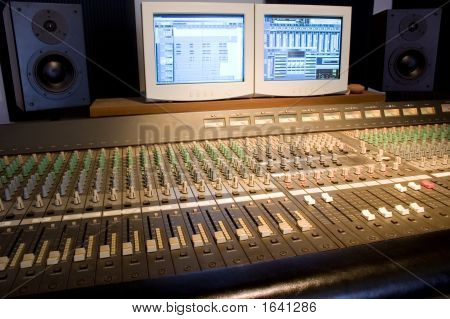 Studio console with computer screens and audio monitors poster