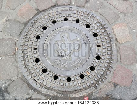 Manhole cover in town of Munster in Germany depicting 350 years of peace