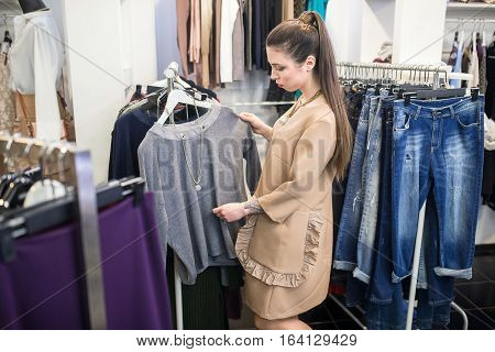Shopper woman choosing clothes thinking looking at clothing while shopping in store.