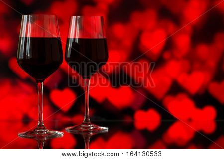Two Glasses Of Red Wine Against Bokeh Background With Sparkles And Roses. Very Shallow Depth Of Fiel