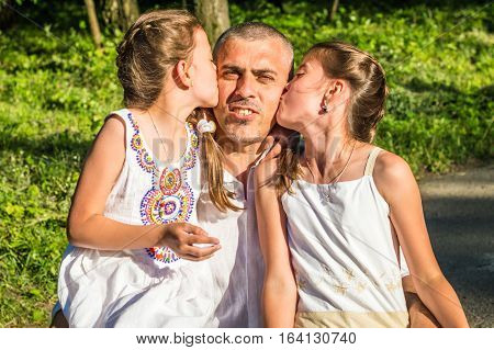 Daddy hugs his daughters in the Park