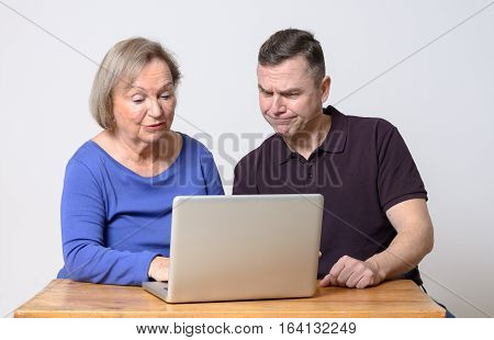 Confused Man And Smiling Woman Using Laptop