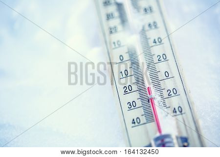 Thermometer on snow shows low temperatures under zero. Low temperatures in degrees Celsius and fahrenheit. Cold winter weather twenty under zero.