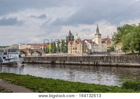 Prague Vltava River Charles Bridge view of the Mala Strana from the right bank . Pleasure boat on the river.