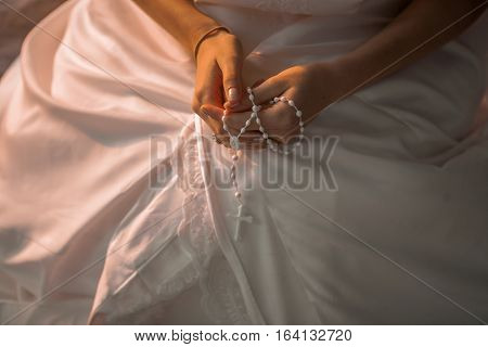the bride holds white little cross in her hands