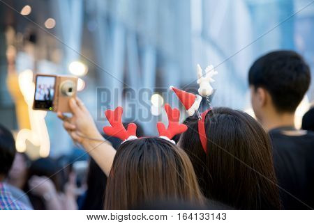 Beautiful young Asian happy woman waring cute hair band enjoying their holiday time together and selfie with friend at christmas and new year holidays.