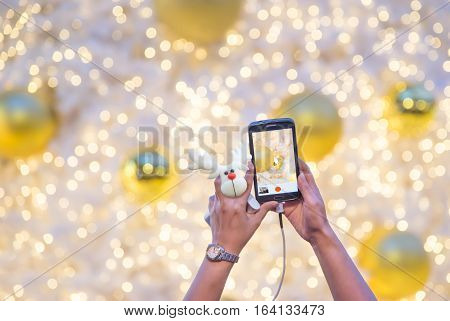 Woman's hand holding mobile phone and reindeer doll take a photo of white christmas tree with golden baubles ball. Traveler using smartphone capture xmas lighting decoration with bokeh blur background