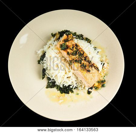Delicious Piece Of Salmon On A Bed Of Long Grained Rice, And Spinach, On A Plate Towards Black