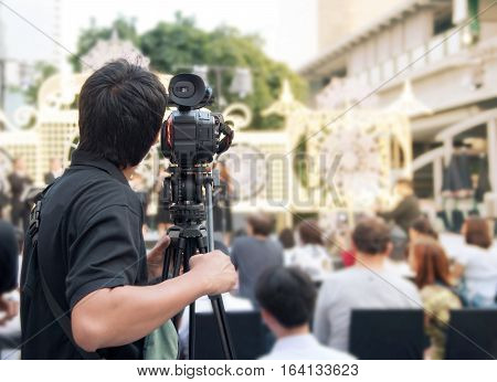 Back of young cameraman using a professional camcorder outdoor filming music show or mini concert with blur background Bangkok Thailand