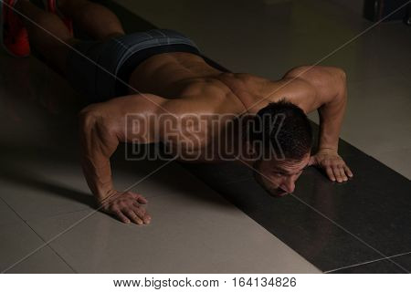 Healthy Man Doing Press Ups In Gym