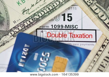 Double taxation agreement concept with form, US dollar bills and credit card