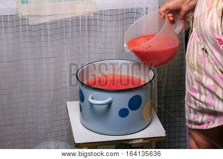 Hand Pouring Tomato Sauce Into The Pot In The Kitchen. Cooking Homemade Tomato Sauce In The Kitchen.