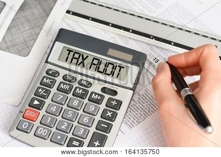 Tax form with pen, envelope and calculator saying tax audit