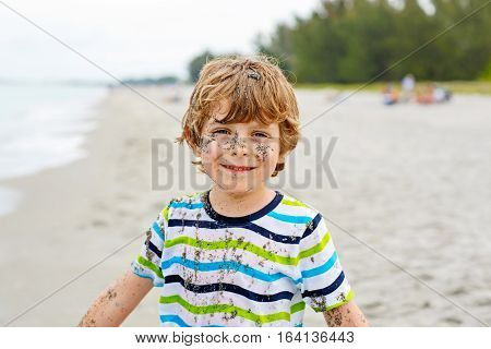 Portrait of happy little kid boy on the beach of ocean. Funny cute child making vacations and enjoying summer. Boy with sand in face, having fun and laughing.