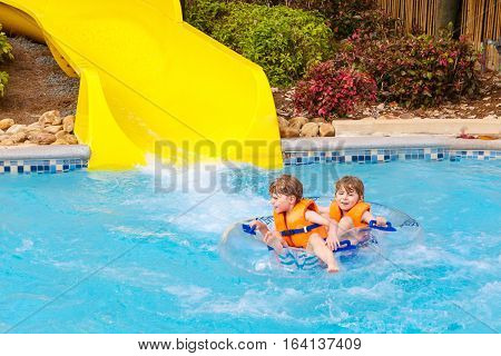 Two funny excited children enjoying summer vacation in water amusement park riding on slide with float. Happy little kids boys having lot of fun together, sliding, laughing.
