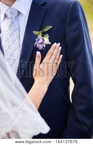 Bride touching suit of groom with boutonniere, closeup