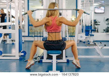 Pretty young woman working out on a fitness station in gym.