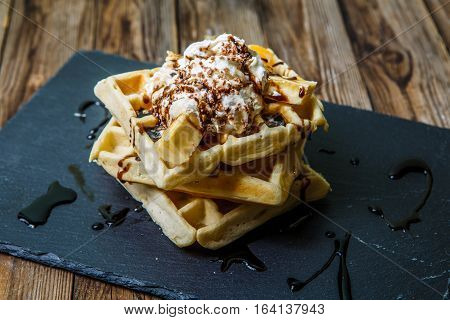 Picture of several Viennese waffles with chocolate, tangerines and ice-cream on blackboard