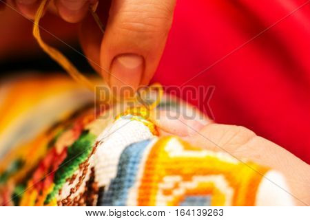 The cross stitching. Photo of woman hands closeup, which holds the needle and the embroidering. Selective focus. 4
