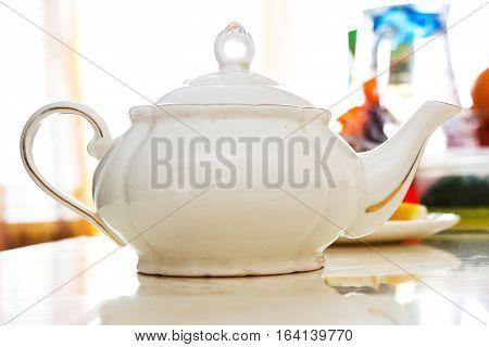 White ceramic teapot on the white table
