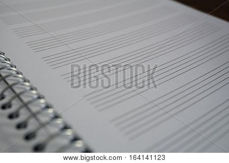 Macro detail of a notepad with paper lined as a piano sheet with lines prepared for composing music