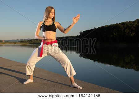 Karate girl practicing shuto uke kokutsu dachi kata on lake near the water