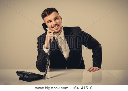 A young man in a black suit dials the phone number while sitting in the office. Manager looking at the camera and talking on the phone