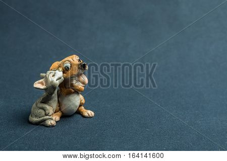 Toy of a dog with a cat against a dark background