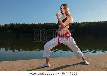 Karate girl practicing zenkutsu dachi ude uke kata on lake near the water