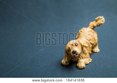 Toy of a dog sat down on forepaws against a dark background