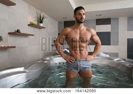 Wellness Spa - Man Flexing Muscles in Hot Tub Whirlpool Jacuzzi Indoors at Luxury Resort Spa Retreat - Handsome Young Male Model Standing Strong in Water Near Pool on Travel Vacation Holiday poster