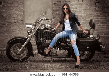 Fashion rocker girl with sunglass sitting on motorcycle