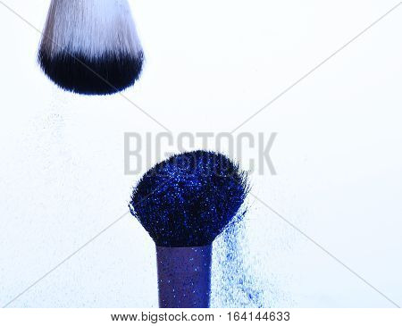 soft cosmetics brushes with blue sparkle glister isolated on white copy space