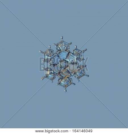 Snowflake isolated on pale blue background: macro photo of real snow crystal, captured on glass with LED back light. This is small stellar dendrite snowflake with glossy relief surface and short arms.