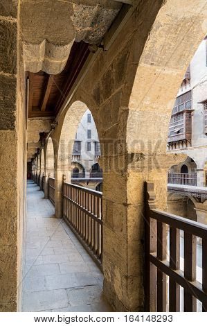 Angled view of one arch with interleaved wooden balustrades at the arcade surrounding the courtyard of caravansary (Wikala) of Bazaraa Medieval Cairo Egypt