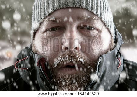 Freezing cold man standing in a snow storm blizzard trying to keep warm. Wearing a beanie hat and winter coat with frost and ice on his beard and eyebrows staring at the camera.