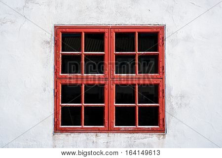 Old red weathered window with squares on white wall with worn texture.