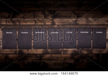 Seven day black chalkboard notices individually hanging from a rustic wooden wall