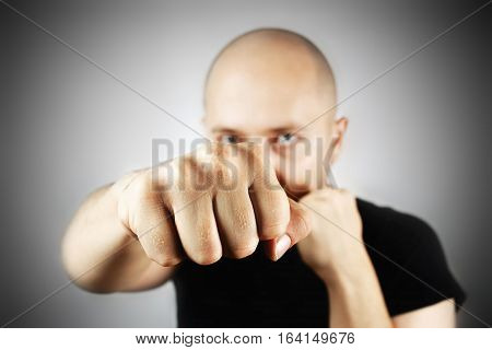 Punch with clenched fist of a young bald man