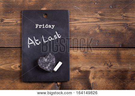 Finished the working week concept. Friday at last notice on a chalk board with chalk and heart shaped eraser. Background set on a rustic wooden boards
