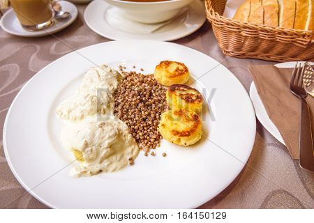 Boiled potato dumplings with onions and cream - Delicious Slovenian food without meat consisting of boiled potato dumplings with onions and cream sauce baked dodole and Buckwheat porridge.