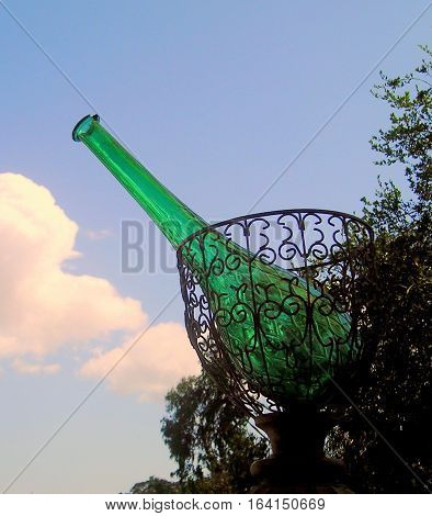 Large wine bottle in a basket abstract outdoors.