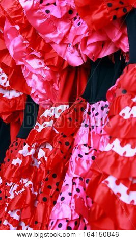 Traditional colorful flamenco dresses for sale in Spain.