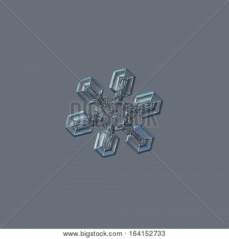 Snowflake isolated on grey background: real photo of medium size snow crystal (around 3 millimeters from tip to tip), resembling duck feet, sparkling on bright gray background.